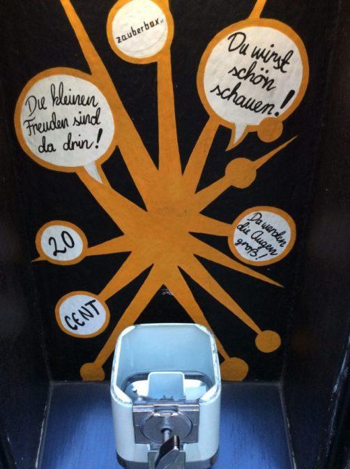 """Hier ist ein alter, nicht mehr funktionsfähiger Kaugummiautomat zu sehen, der kleine Überraschungen enthielt. Auf der Wand dahinter stehen Werbesprüche wie """"Die kleinen freuden sind da drin"""" und """"Du wirst schön staunen"""""""
