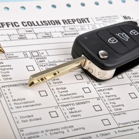 Accident report with key and pen after autonomous car crash