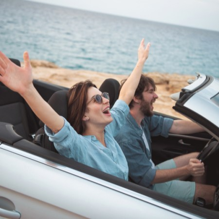 Couple rides in beach in convertible with top down, woman's hands thrown up wide