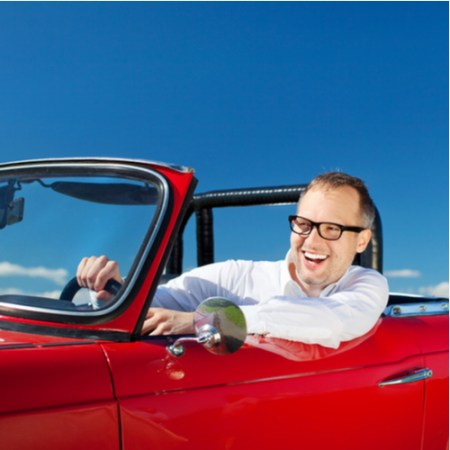 Happy man driving red convertible