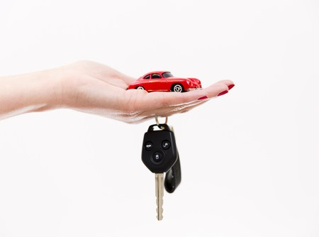 toy car in outstretched hand with keys symbolizes new car purchase