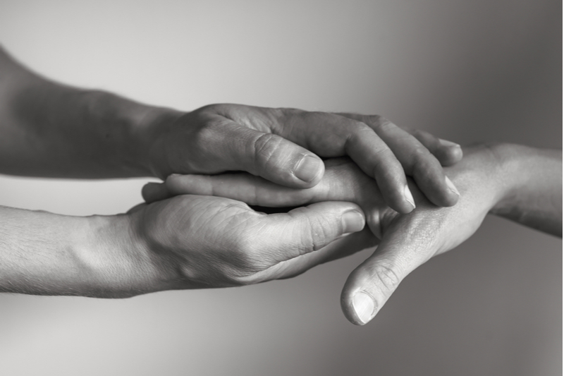 hands holding hands to suggest empathy and acts of kindness