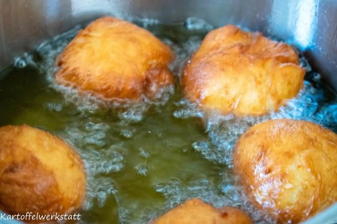 Kartoffelkrapfen schwimmen im Frittierfett