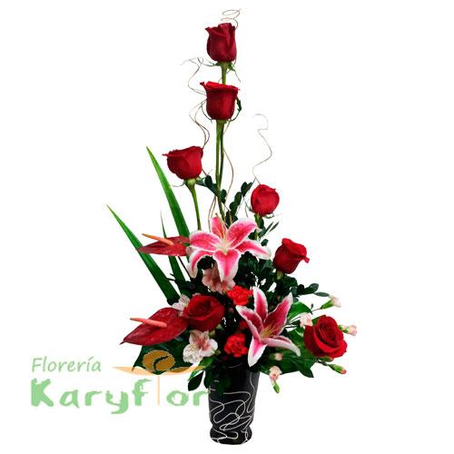 Arreglo floral elaborado en base de cerámica. Contiene 7 rosas