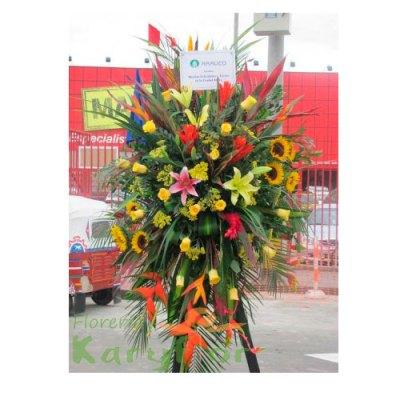 Arreglo floral compuesto por finas rosas,girazoles, lilium, eliconias, esterlicias, ginger, variedad de flores, palmeras y fino follaje elaborado en tripode. Incluye tarjeta de dedicatoria.