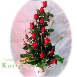 Arreglo floral elaborado con 12 rosas, variedad de flores, verónicas y fino follaje en base de cerámica. Incluye tarjeta de dedicatoria.