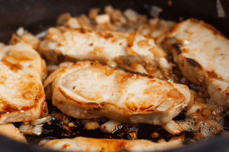 pork chops searing in a cast iron skillet