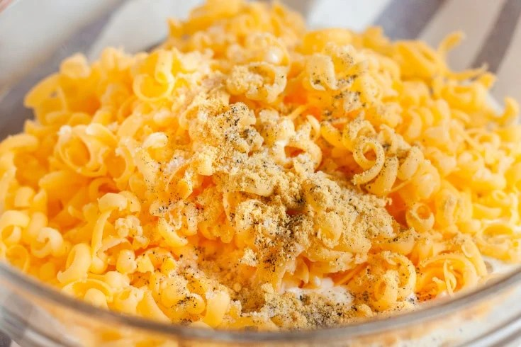 bowl of egg mixture with shredded cheese and seasonings on top for low carb egg bake