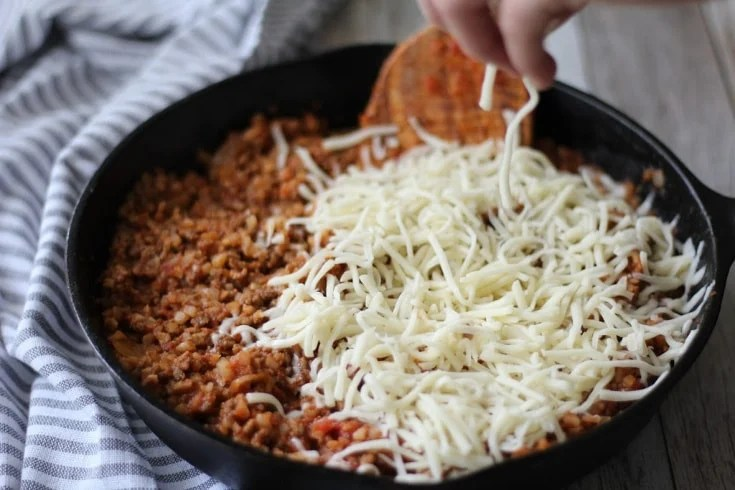 Beef mixture with mozzarella cheese being sprinkled over the top.