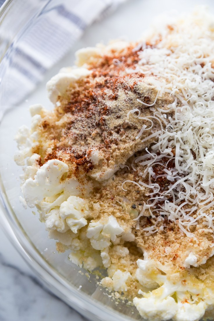 Cauliflower florets being mixed with pork panco bread crumbs, olive oil, parmesan cheese, and spices.