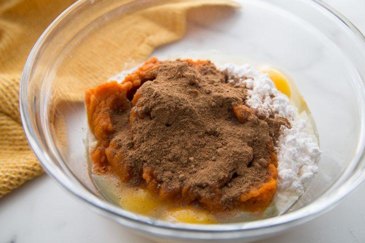clear bowl with pumpkin puree, sweetener, eggs, etc