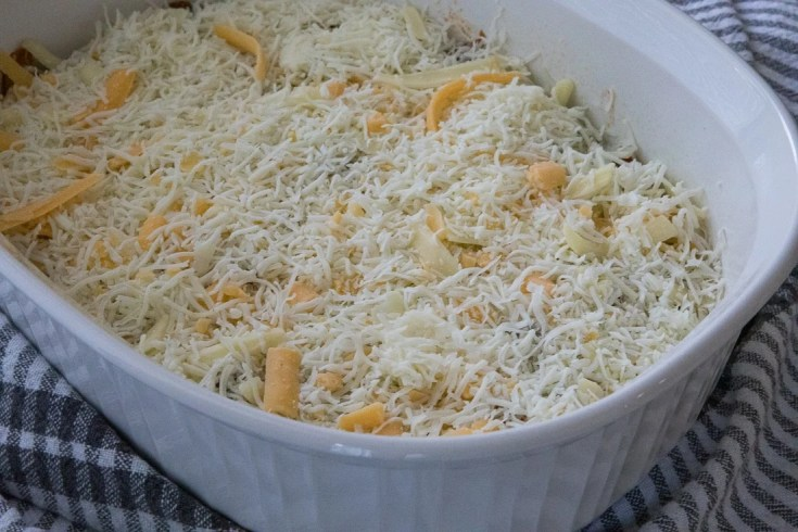 ketogenic chili in a casserole dish with cheese on top before it goes in the oven