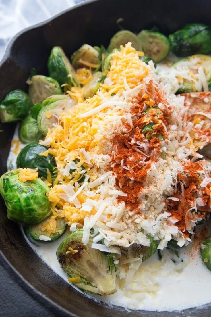 Brussels sprouts with cheeses and spices added to the skillet