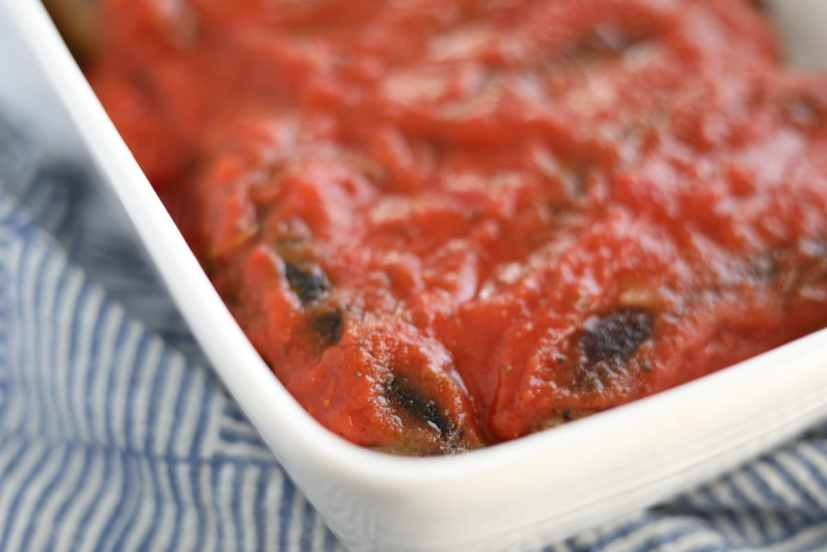 tomato sauce over sausages in a baking dish