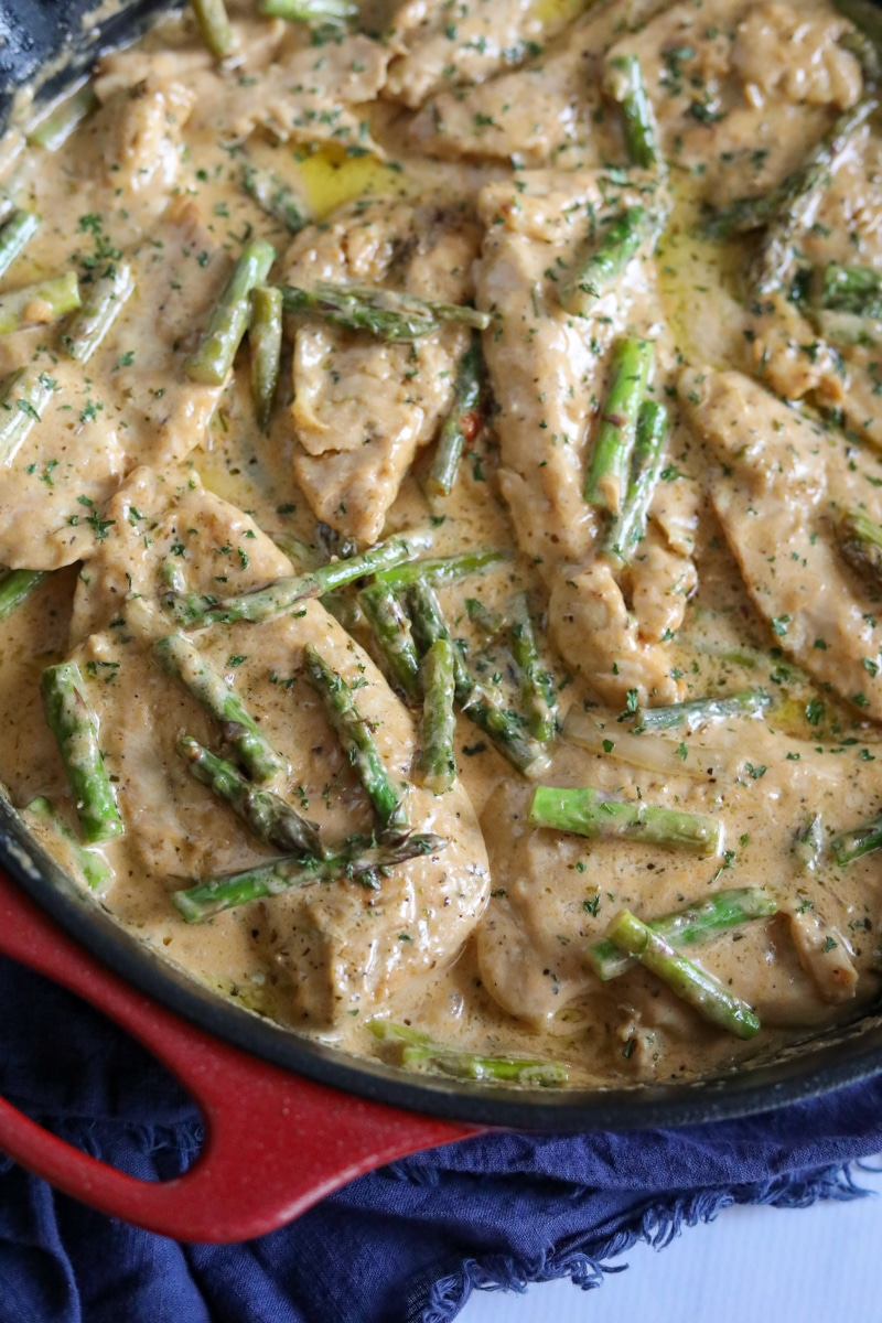 chicken and asparagus in cream sauce in a skillet