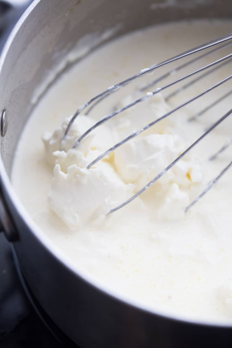whisking cream cheese sauce in saucepan
