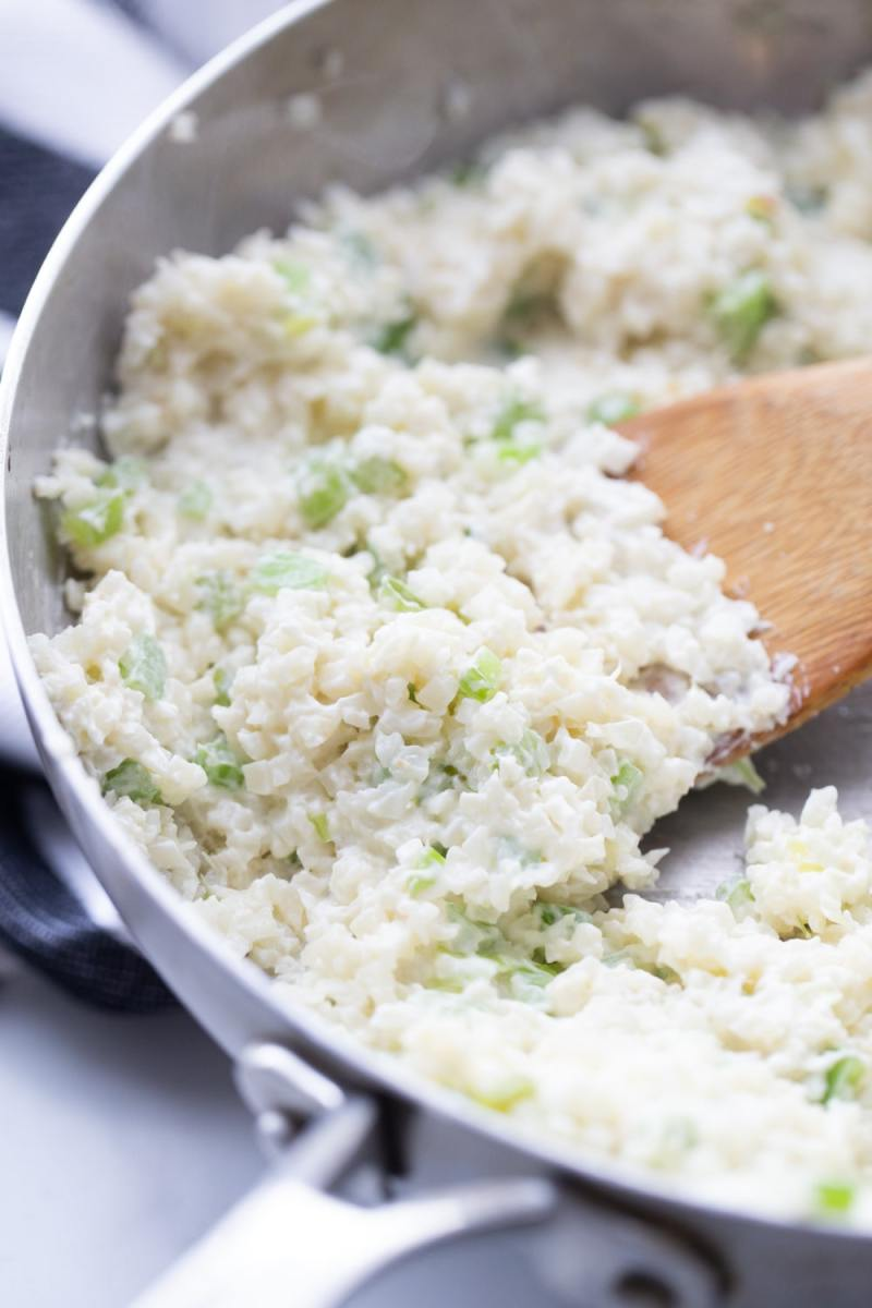 Cream cheese, riced cauliflower, celery sauteed in a skillet.