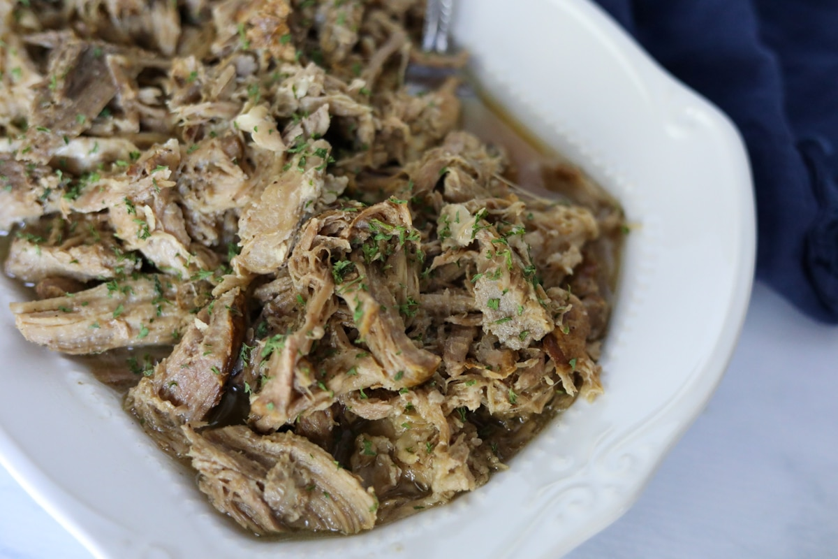 low carb pork roast shredded on a white plate in juices