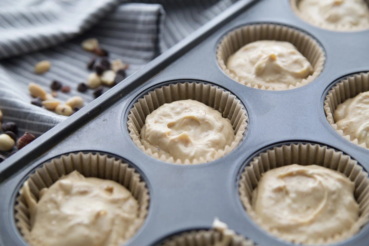 raw cheesecake batter in a muffin tin lined with cupcake liners