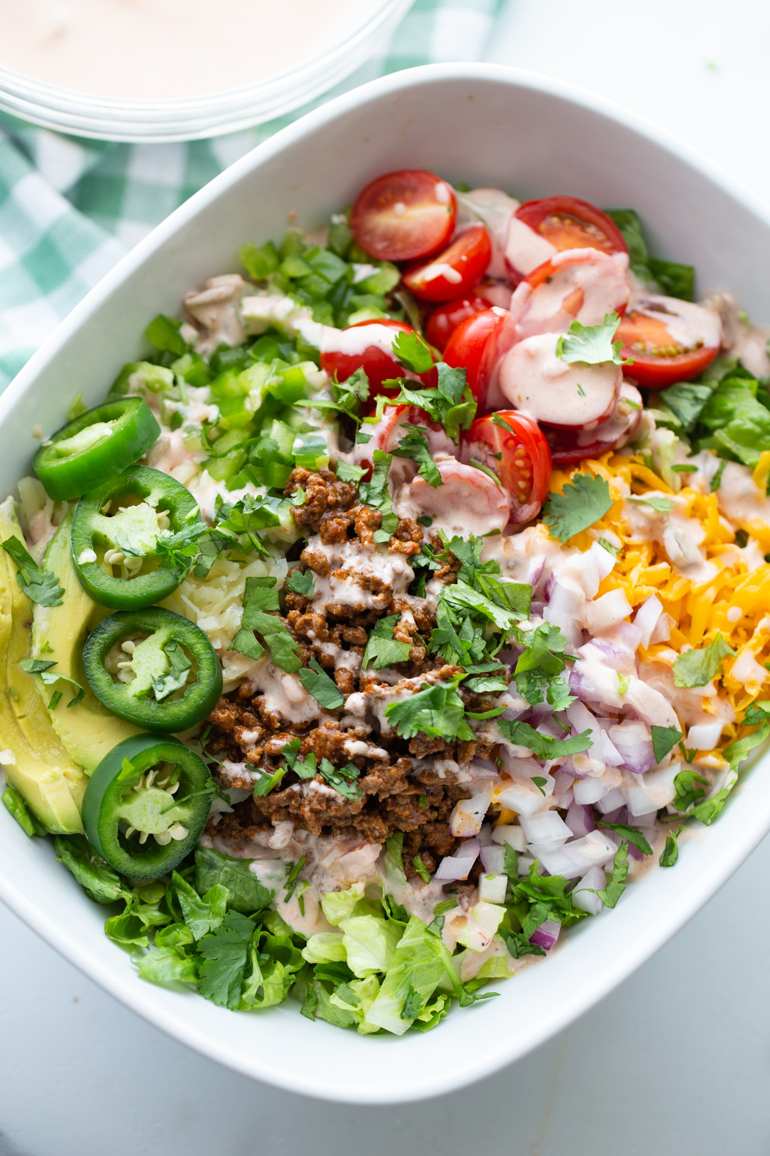 taco salad without tortilla shell in a white bowl with dressing