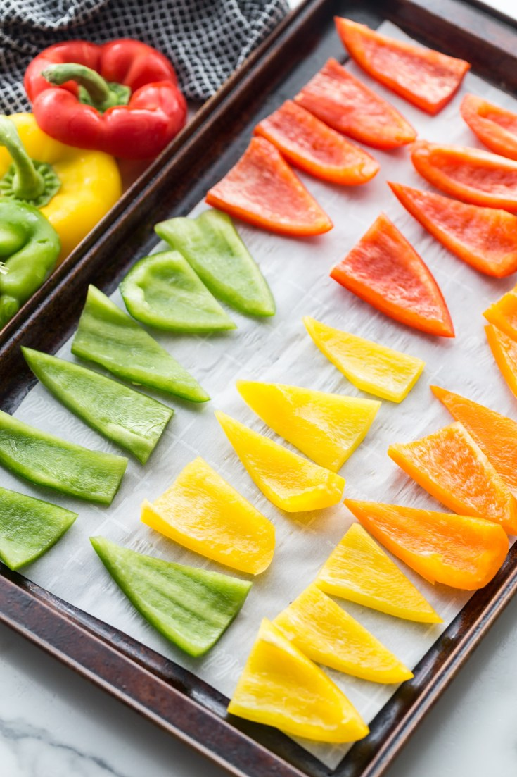 red yellow gree and orange sliced bell peppers on a baking sheet