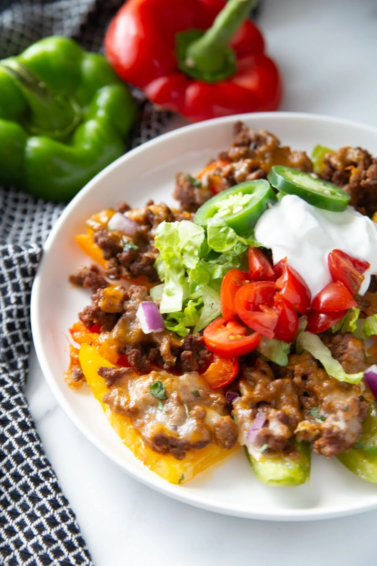 low carb nachos on a white plate with ground beef, cheese and veggies