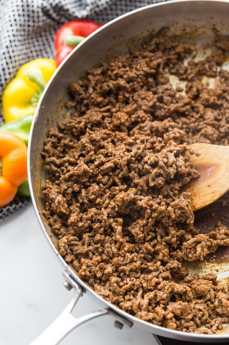 ground meat in a skillet with taco seasoning and wooden spoon