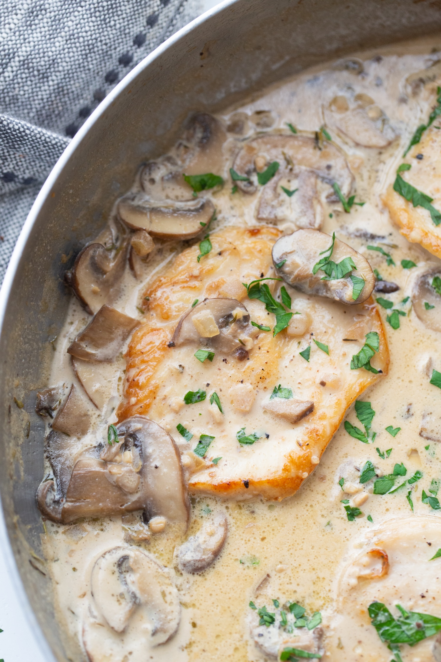creamy keto chicken marsala in a skillet with fresh parsley on top