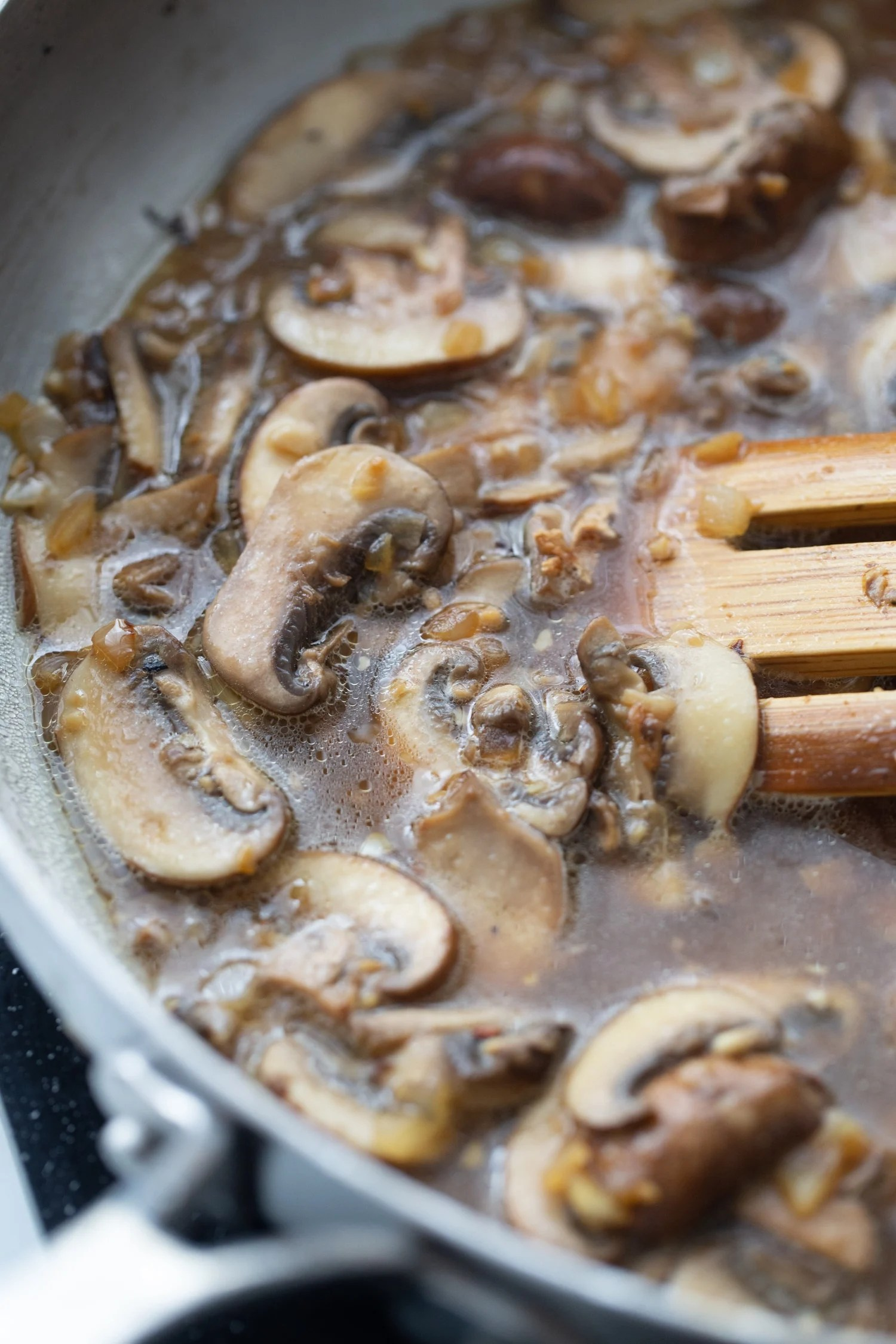 sliced mushrooms in a skillet with chicken stock