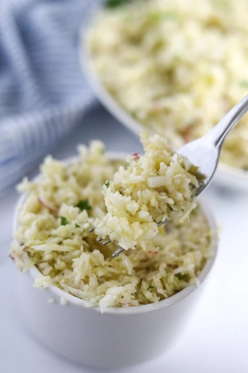 Keto Coleslaw in a small bowl with a bite on a fork