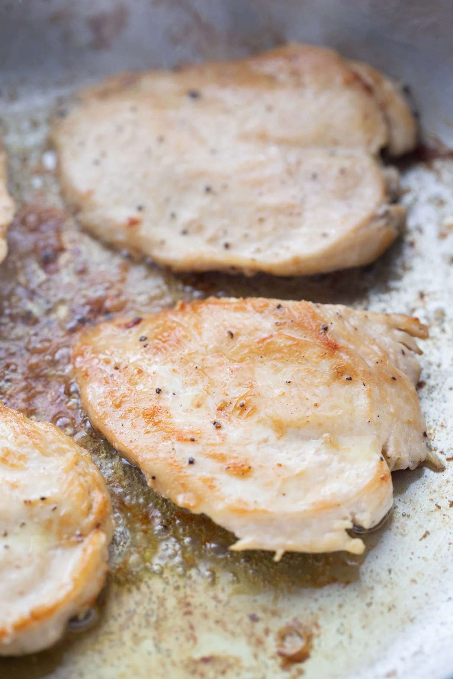 seared chicken cutlets in a pan