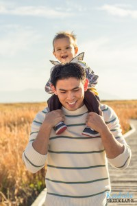 Image of little boy being carried on his father's shoulders on a boardwalk for Welcome to Kashele Photography Blog