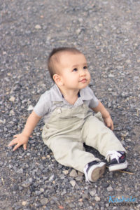 little boy in a fedora and overalls looking up while sitting on the ground with rocks