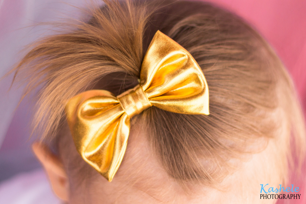 Miss Thomas' First Birthday Session: Close up image of baby's ponytail and golden bow