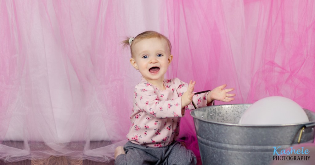 Image of baby girl sticking her hand through the handle of a metal washtub from Miss Hardy's First Birthday Session