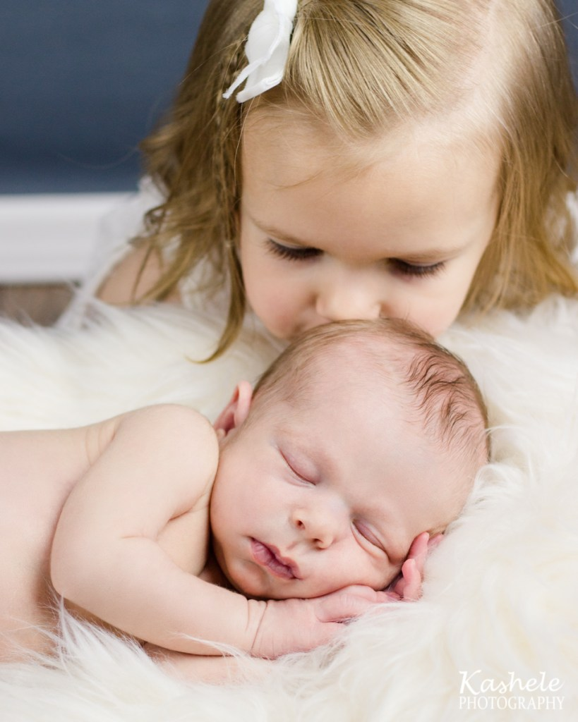 Big sister kissing baby brother's head