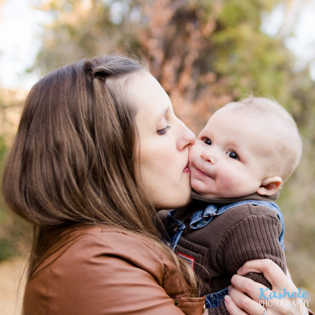 Mom kissing baby brother on the cheek