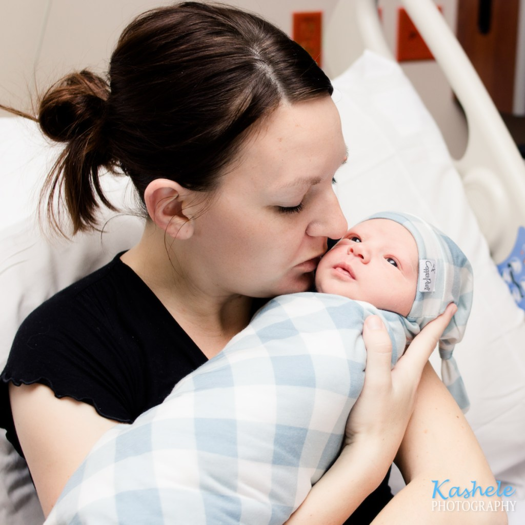 Alexis kissing her rainbow baby after her birth story
