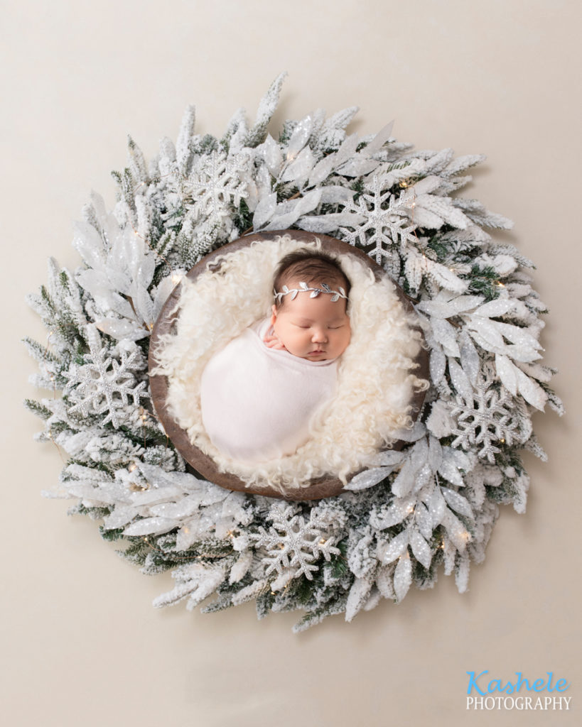 Picture of baby nestled in a white winter wreath for Eagle Mountain Newborn Photography post