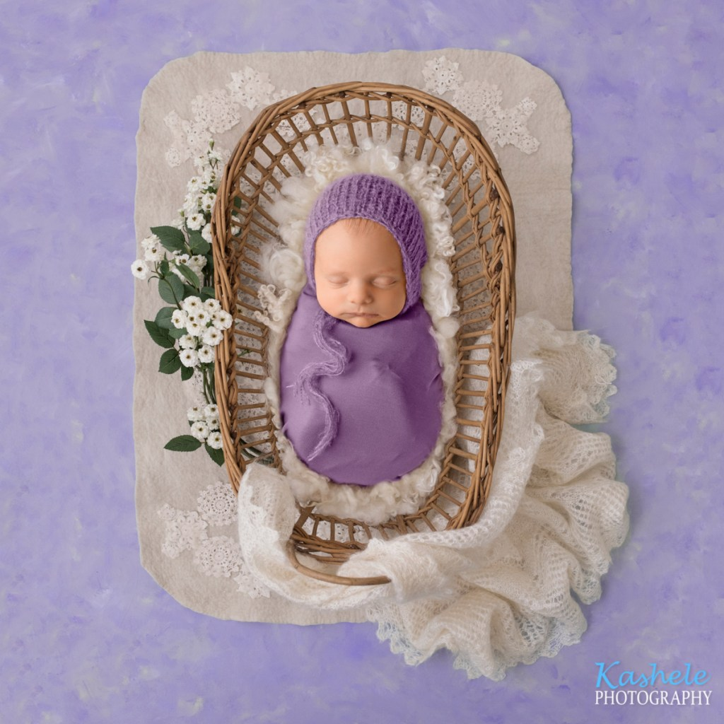baby swaddled in purple