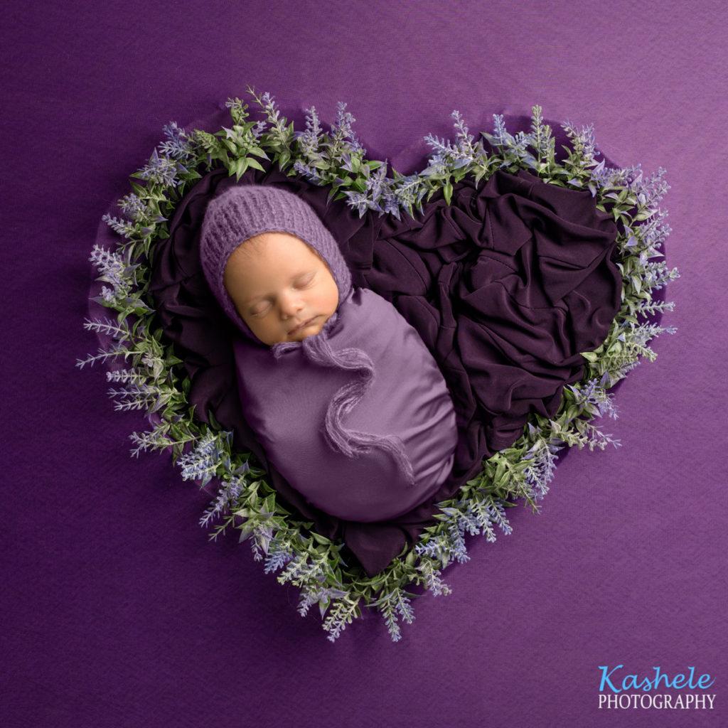 Baby in lavender heart for Logan Newborn Photographer post