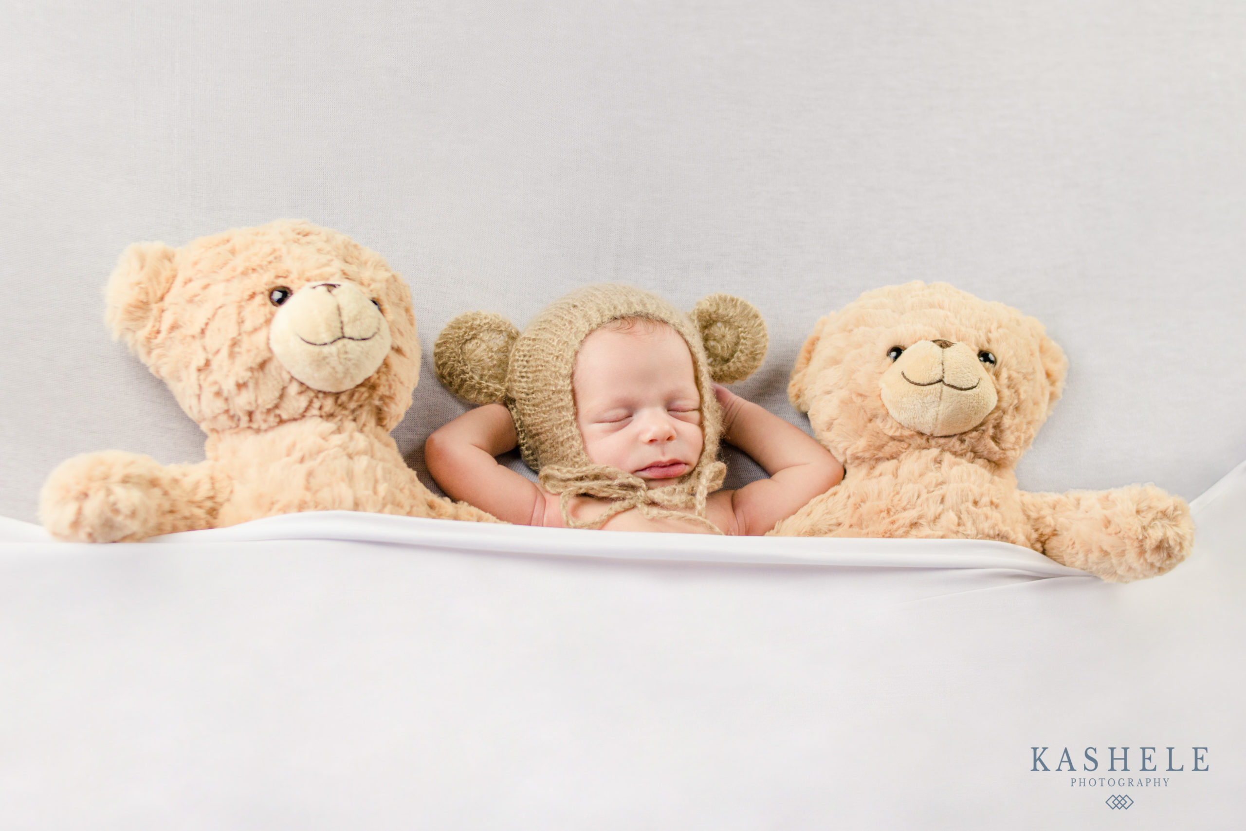baby boy tucked into bed with his teddy bears