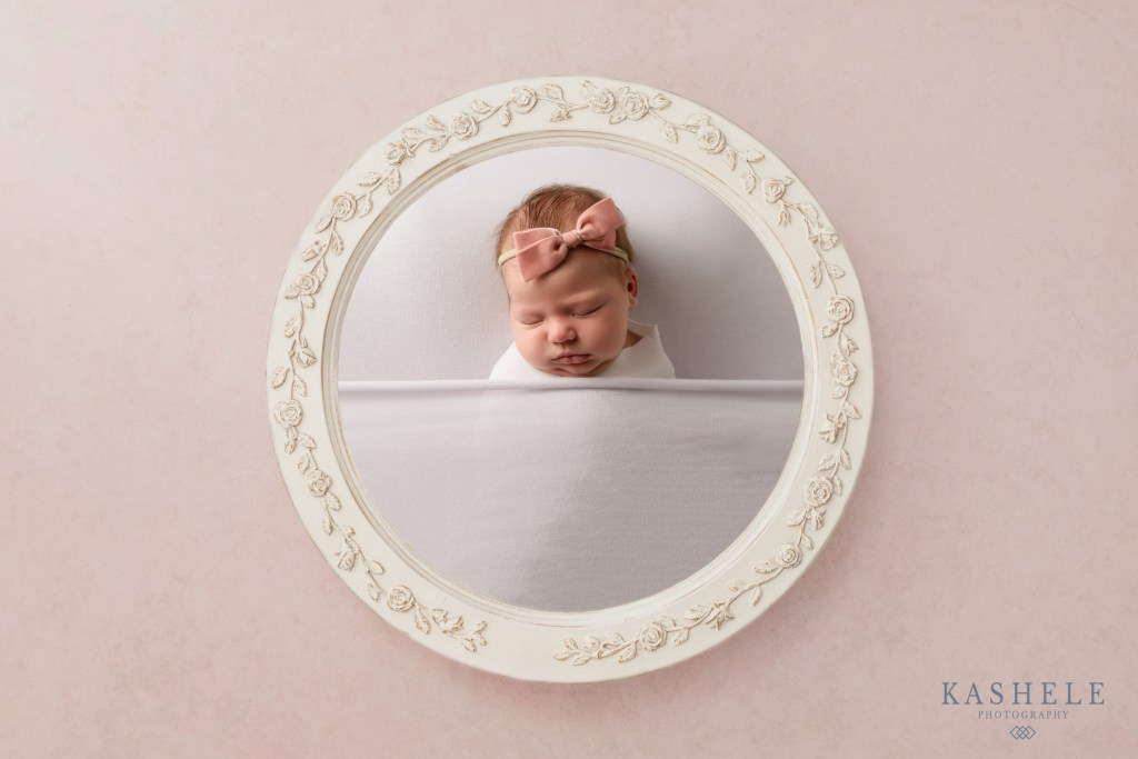 Baby girl tucked into bed in a vintage frame