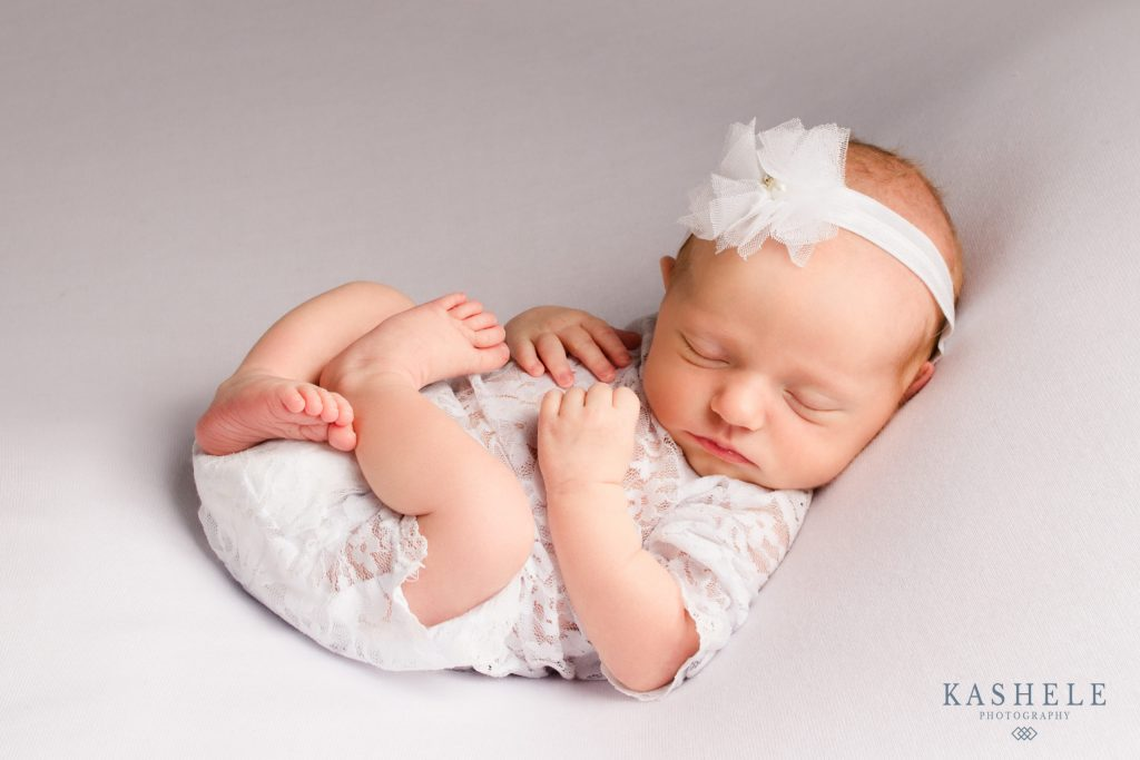 Newborn baby in white for Home Milestone and Newborn Photographer in Utah