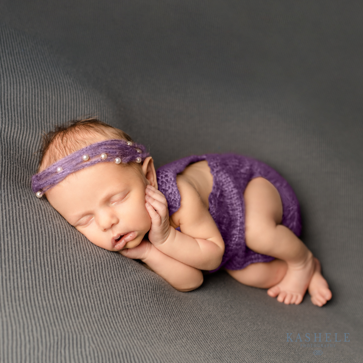 Baby with her hands on her cheeks for for Questions to ask your newborn photographer post