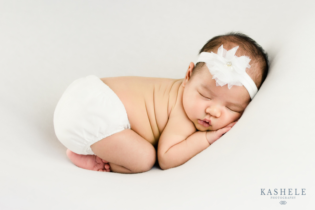 Baby girl in bum up pose for professional newborn photographer post