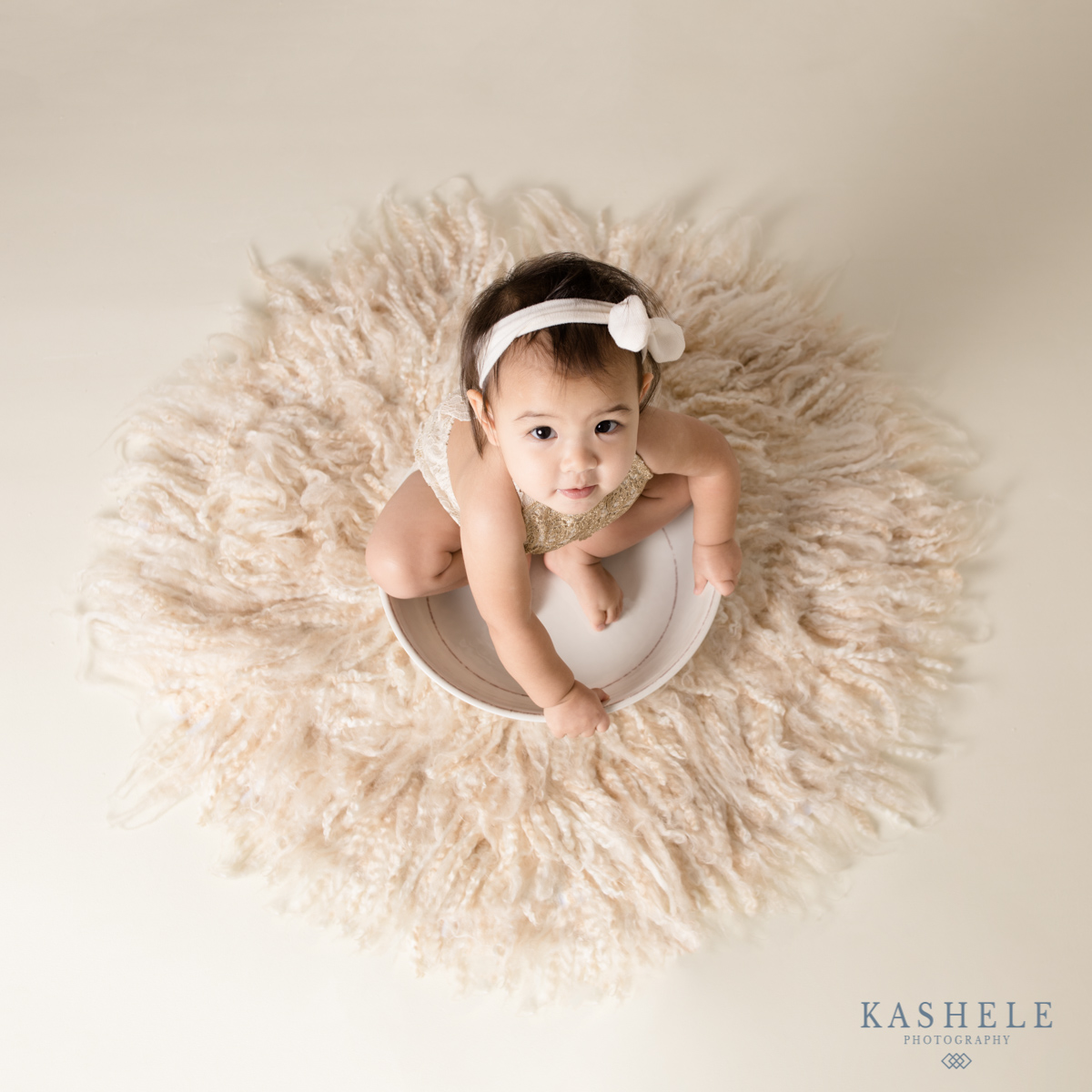 Image of little girl in bowl surrounded by fluff for Why schedule a milestone session post