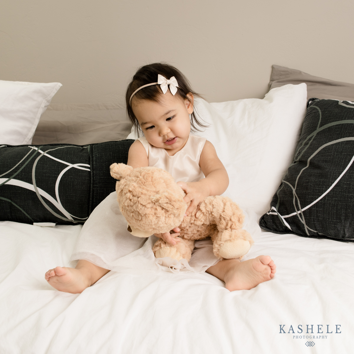 Little girl playing with a teddy bear wearing a hairbow from mini sailor bow from Sweet Ellie Mae Shop