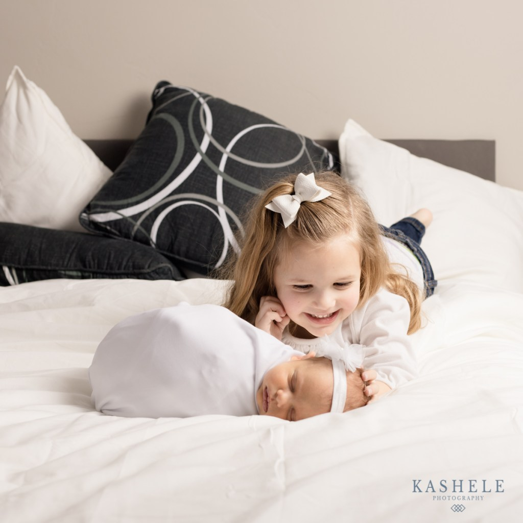 Image of newborn baby with her big sister for custom experience post
