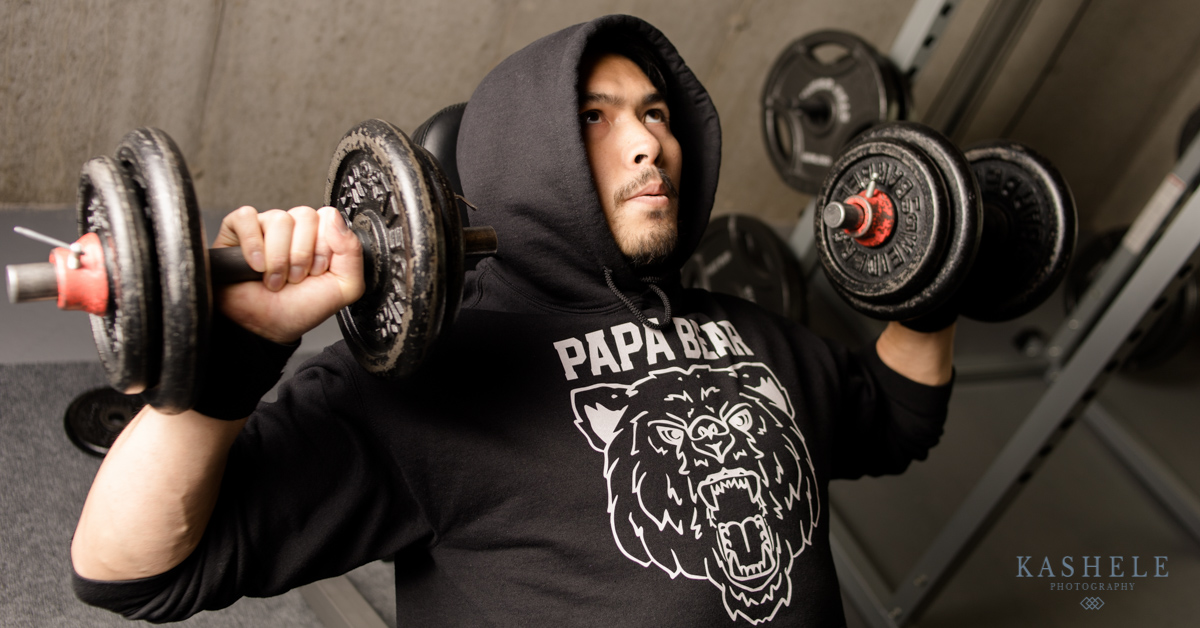 Man doing bench press in papa bear hoodie